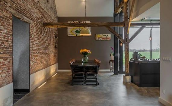 kreative raumbeleuchtung mit bodeneinbauleuchten im esszimmer mit  poliertem betonboden, ziegelwand mit estrichsockel, graue akzentwand mit vintage schildern,rustikale pendellampe über esstisch mit lederstühel im industrial stale