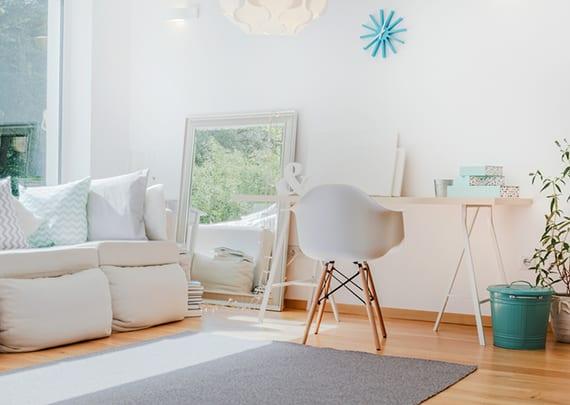kleines helles wohnzimmer mit weißem interieur modern einrichten mit polstersofa vor großem fenster, arbeitsbereich mit weißen stuhl und holzschreibtisch, kreative zimmerdeko mit großem spigel,blauen metalleimer, wanduhr blau