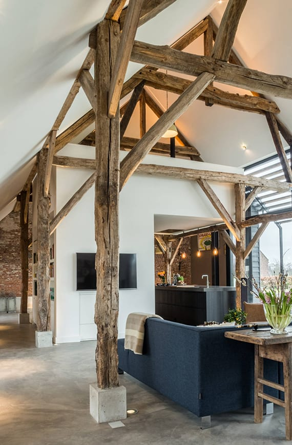 moderne raumgestaltung einer maisonette wohnung mit dachschrägen und dachstuhl, glasfassade und backsteinwand