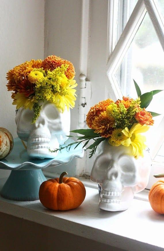 coole fensterbank deko zu halloween mit weißen totenkopf-blumenvasen und orangen kürbissen