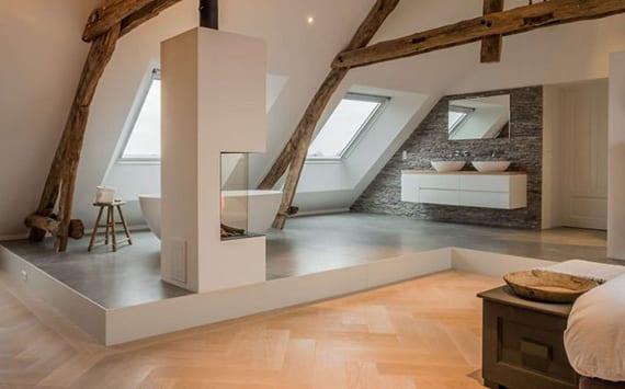 luxuriöses Schlafzimmer mit parkett,bad auf podest mit grauen bodenfliesen, freistehender badewanne unter dachfenstern und doppelwaschbecken an wand mit natursteinwandverkleidung