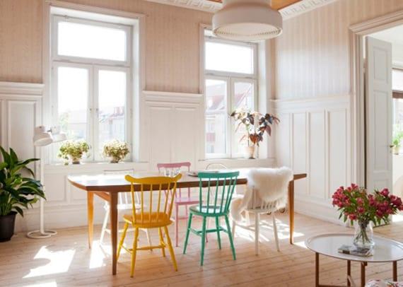 nordische esszimmergestaltung mit natürlichem holboden, weißer wandverkleidung, tapeten in pastellrosa, esstisch aus massivholz mit rustikalen holzstühlen in gelb, blau, weiß und rosa
