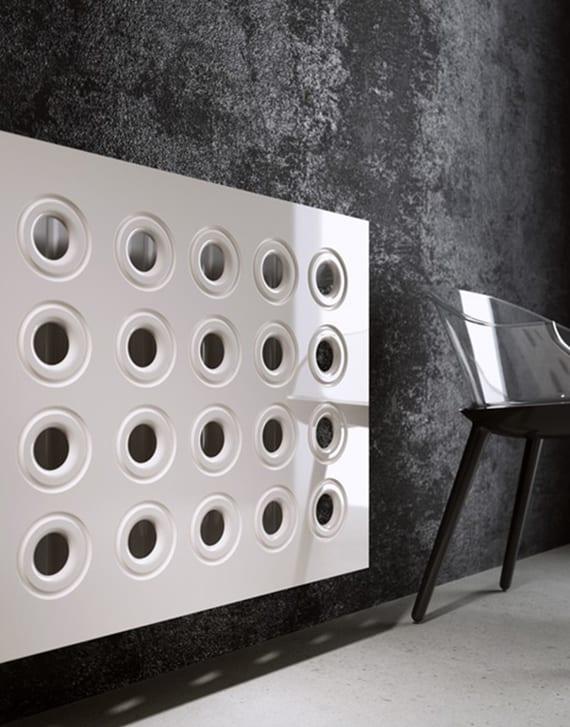 minimalistische raumgestaltung mit schwarzer wand, betonboden und weißer heizungsverkleidung gelöchert