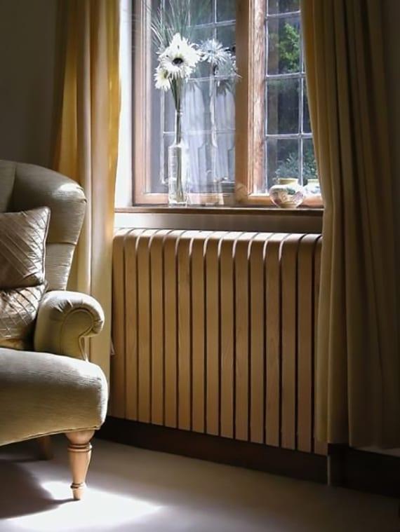 wohnzimmer gemütlich einrichten barock-sessel vor holzfenster mit gelben gardinen und holzverkleidetem radiator
