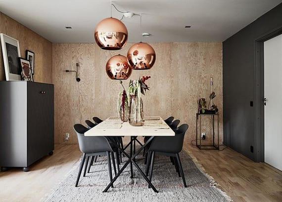 schickes esszimmer interior design in dunkelgrau und holz mit drei kugelhängelampen in Bronzefarbe über weißem esstisch mit dunkelgrauen stühlen