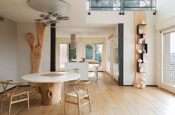 coole wohnideen esszimmer mit hellem holzbodenbelag, offener küche weiß mit kochinsel, rundem esstisch aus baumstamm und weißer tischplatte, designer holzstühlen und kreative wandgestaltung mit holz und diy bücherregal