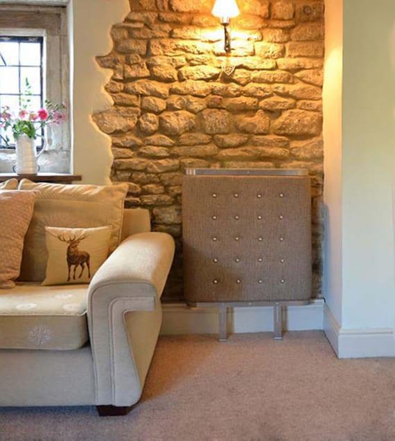 rustikales wohnzimmer einrichten mit polstersofa beige, teppichboden und textil-heizköperverkleidung an steinwand