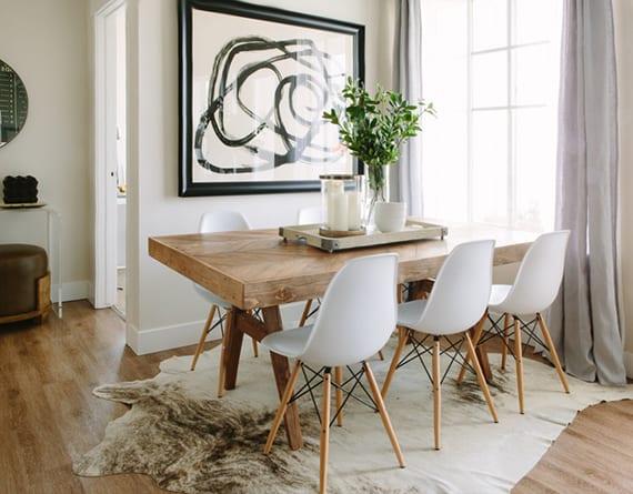 gemütliche farbgestaltung esszimmer mit wandfarbe weiß, grauen gardinen, schwarzem bilderrahmen, massivholztisch mit weißen esszimmerstühlen,kuhfellteppich weiß