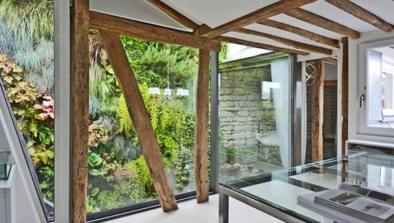 wohnidee für kleines home-office im dachgeschosswohnung mit schiebeglastür zum hofgarten, wießem bodenbelag und glasbürotisch