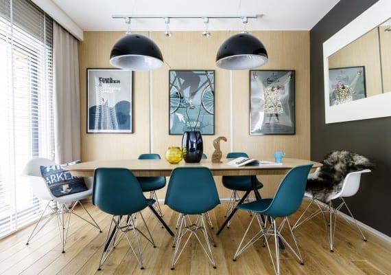 kleines esszimmer modern gestalten mit hellem holzboden, holzwandpaneelen, schwarzer wandfarbe und schwarzen hängelampen über holzesstisch mit blauen stühlen und wanddeko mit wandspigel im weißen rahmen