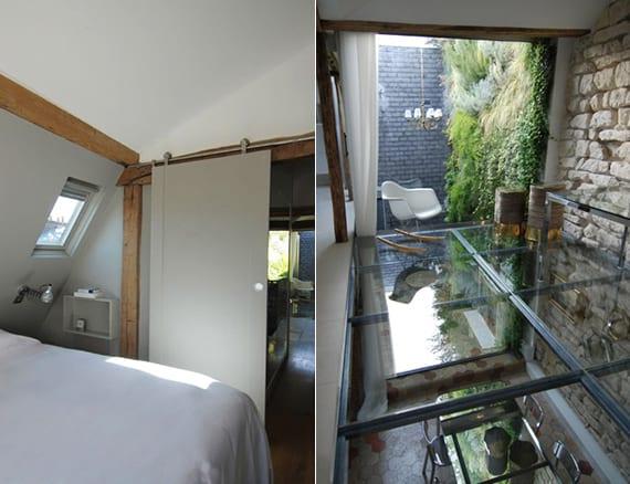 schlafzimmer mit kleinem dachfesnter, nachttisch an der wand und schiebetür zum wohnbereich einer maisonette