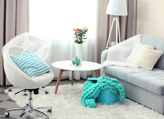 wohnzimmer farbgestaltung mit grauen vorhängen, weißen gardinen, teppich , stehlampe und rollstühlen leder, kleinem sofa hellblau, rundem holzcouchtisch weiß und wohnaccessories im türkis