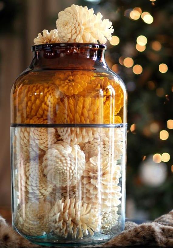 weiße DIY deko mit geblichenen nadelbaumzapfen in großer glasvase als passende dekoidee für herbst und winter