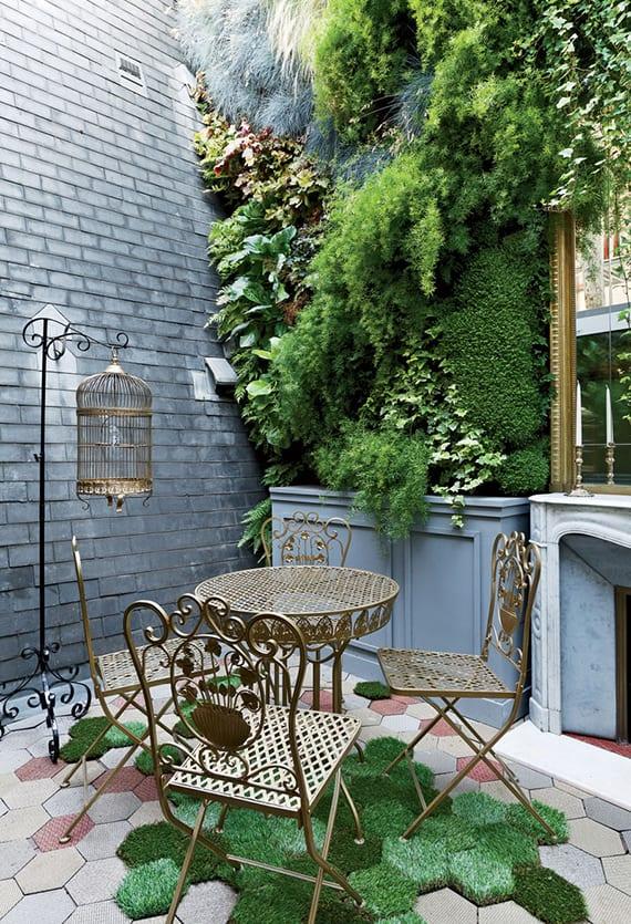 gestaltungsidee für hofgarten einer maisonette mit marmor-kamin, hexagon bodenfliesen und grasfliesen, antikem ständer mit vogelkäfig, metallgartenmöbel gold und begrünter wand