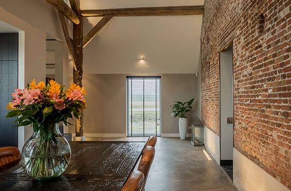 originelles interieur design mit mauer aus roten ziegeln, weiße dachschräge, holzbalken und bodenbeleuchtung mit einbauleuchten
