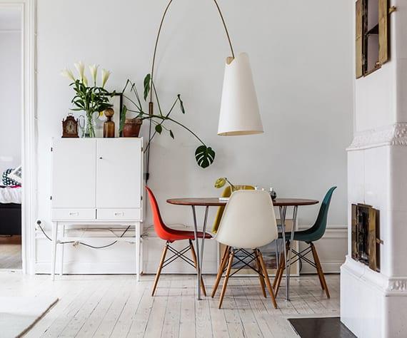 skandinavisches interieur design in weiß mit rustikalem kamin, holzboden, ovalem holzesstisch, bunten esszimmerstühlen, moderner bogenlampe und frischer sideboard deko mit grünen pflanzen und rustikalen dekoaccessories