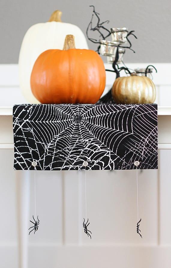 coole bastelidee für DIY Tischläufer mit Spinnennetz für moderne kürbis Halloween Tischdeko in schwarzweiß mit spinen und baum-teelichthalter