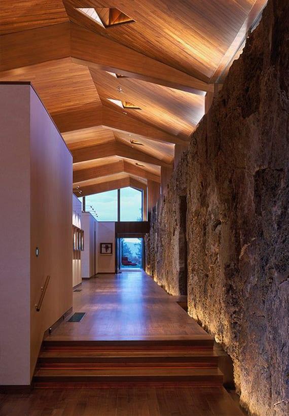 luxus haus interieur design mit indirekter wandbeleuchtung entlang steinmauer, parkettboden, holzdeckenverkleidung und natürliche raumbeleuchtung durch kleinen dachfenster