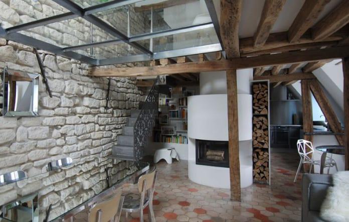 maisonette wohnung mit glasdecke über esstisch aus spigelglas und alustühlen, akzentwand aus kalkstein, hexagon bodenfliesen und kamin rund
