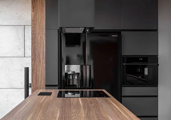 moderne küche grau mit kochinsel, schwarzem kühlschrank, küchenarbeitsplatte holz und betonwand aus paneelen