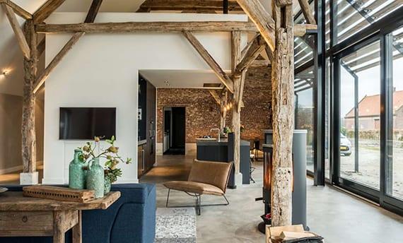 moderne raumgestaltung wohnzimmer mit küche schwarz,poliertem betonboden, ziegelwand, skandinavischem kamin, modernem sofa blau und holzbalken