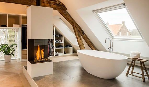 modernes schlafzimmer gestalten mit offenem schranksysten, kamin, weißer badewanne freistehend, hellem parkettboden und grosformatigen badfliesen grau