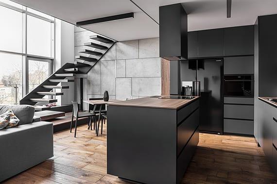 gestaltungsidee für wohnzimmer mit offener küche und kochinsel in graphite, weißer decke mit länglichen deckenleuchten und metalltreppe zum arbeitsbereich