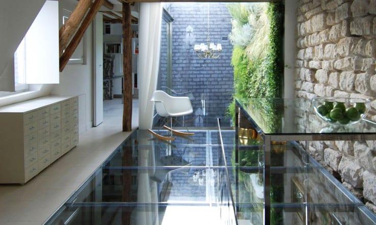 moderne gestaltung einer Doppeletagenwohnung mit dachschräge, inneren fensterläden weiß,verglastem boden und blick auf kleinem hofgarten mit vertikaler begrünung