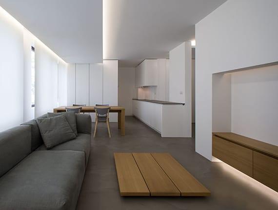 minimalistisches wohnzimmer interieur design mit poliertem betonboden, weißen wänden, polstersofa grau, niedrigem holzcouchtisch und TV-Regal holz, esstisch aus massivholz,indirekter deckenbeleuchtung, weißen schiebegardinen