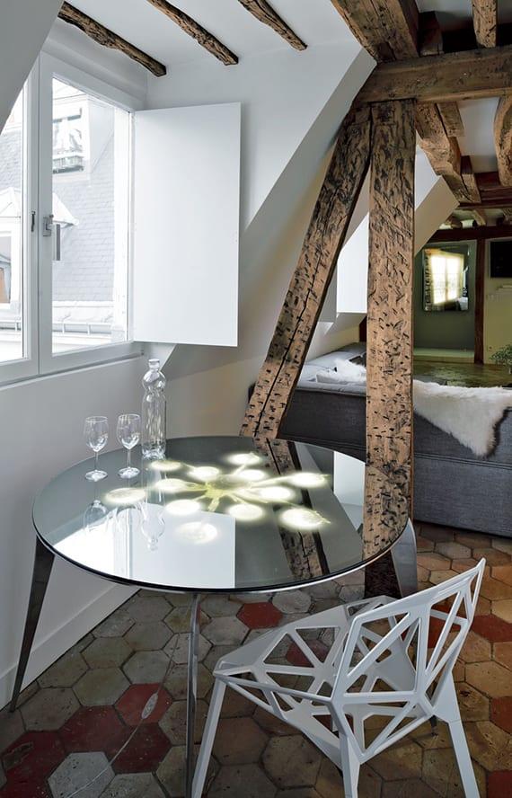 kleine essecke im wohnzimmer einer maisonette mit rundemEsstisch aus alu und spigelglas und designer stuhl weiß vor gaubenfester mit weißen fensterläden