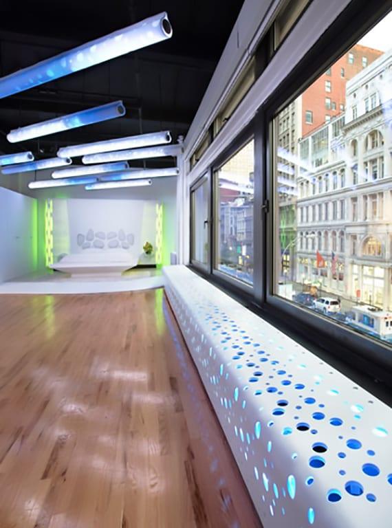 gestaltungsidee für große und offene büroräume mit holzboden, modernen hängelampen und indirekt beleutetem heizköprer mit gelöcherter verkleidung aus acrylstein