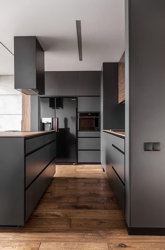 offene küche im wohnzimmer mit holzboden, schwarzen küchengeräten, dunkelgrauen küchenschränken, decken dunstabzugshaube über kochinsel und weiße decke mit einbauleuchte