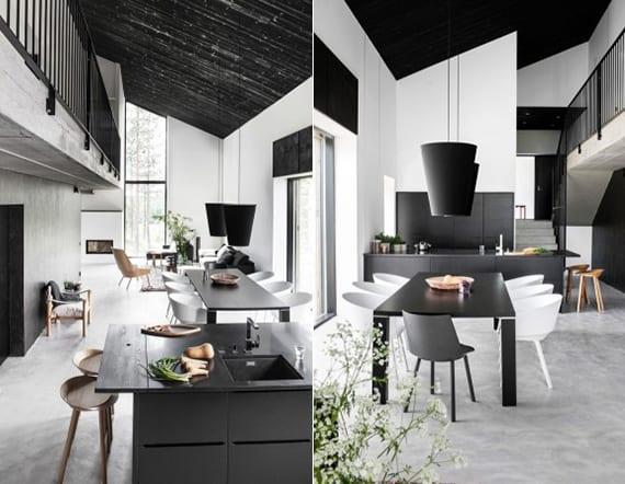 minimalistisches wohnzimmer mit betonboden,schwarzer deckenverkleidung holz,einbaukamin, wohnküche mit kochinsel schwarz, esstisch schwarz mit weißen stühlen und modernen hängelampen schwarz