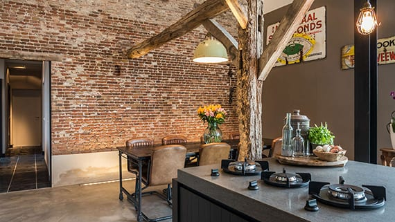 offene küche im industriellen stil mit kochinsel, holzesstisch mit brauenen lederstüglen, vinatge pendellampen, ziegelwand mit sockel, wandfarbe grau und betonboden