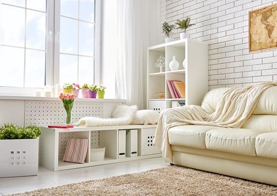 kleines Wohnzimmer kreativ und praktisch einrichten mit weißen kallax regalen als sitzplatz vor dem fester, weißer kiste als blumentopf und beige teppich vor creme ledersofa, wand gestalten mit weißer ziegeltapete