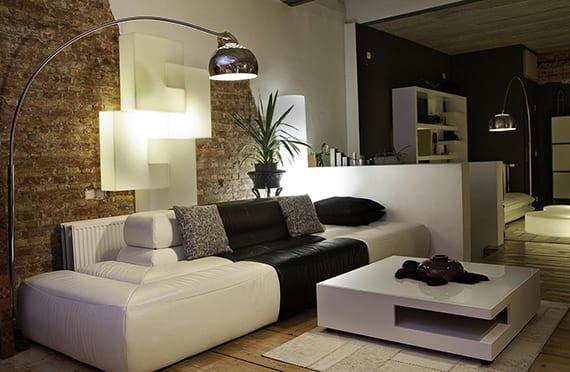 kreatives und modernes lichtdesign für kleines wohnzimmer mit bogenleuchte und moderner wandlampe weiß_wohnzimmergestaltung mit kalksteinwand, holzboden, 3-er Ledersofa weiß und schwarz mit rechteckigem couchtisch weiß