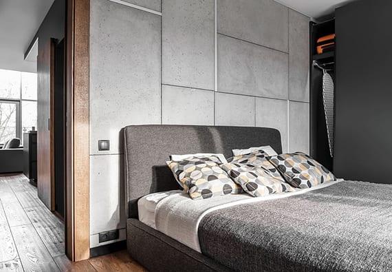 kleines schlafzimmer minimalistisch gestalten in grau und schwarz mit akzentwand aus betonplatten, schwarze fußleiste, parkett und doppelbett grau