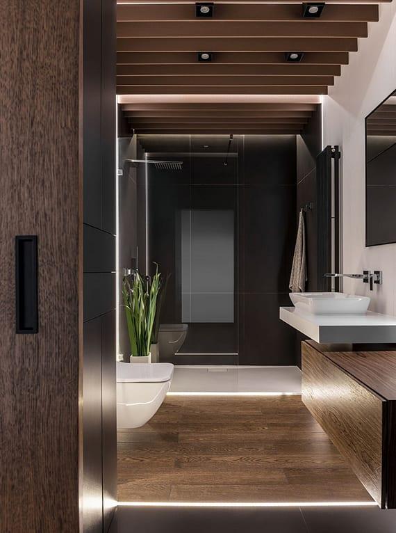 kleines Luxus Bad mit bodenbeleuchtung, bodengleicher Duschtasse weiß, heizkörper schwarz, holzbadezimmerschrank mit waschbecken aus glas und deckengestaltung mit holzlamellen