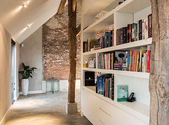 kreative raumgestaltung und raumtrennung mit eingebautem Bücherregal weiß, holzstützen mit betonsockel, dachschräge mit punktbeleuchtung und graue wand mit weißer fußleiste