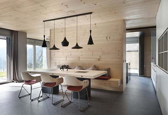 luxuriöses wohnzimmer mit einbauküche weiß, grauen bodenfliesen, trennwand holz mit sitzbank, modernem esstisch aus holz und metall, designer pendelleuchten schwarz und deckenverkleidung holz