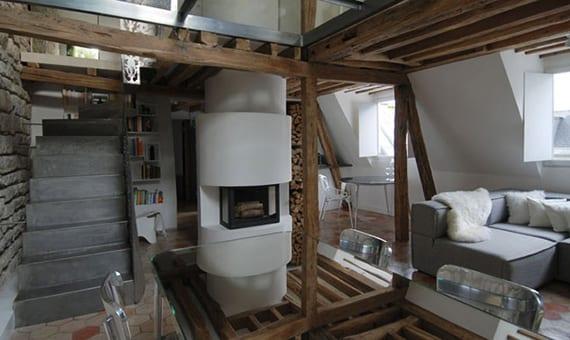 modernes wohn-esszimmer mit kamin rund, weißen wandregalen, ecksofa grau, esstisch mit spigeltischplatte und stahlblechtreppe in maisonette wohnung mit holzbalkendecke