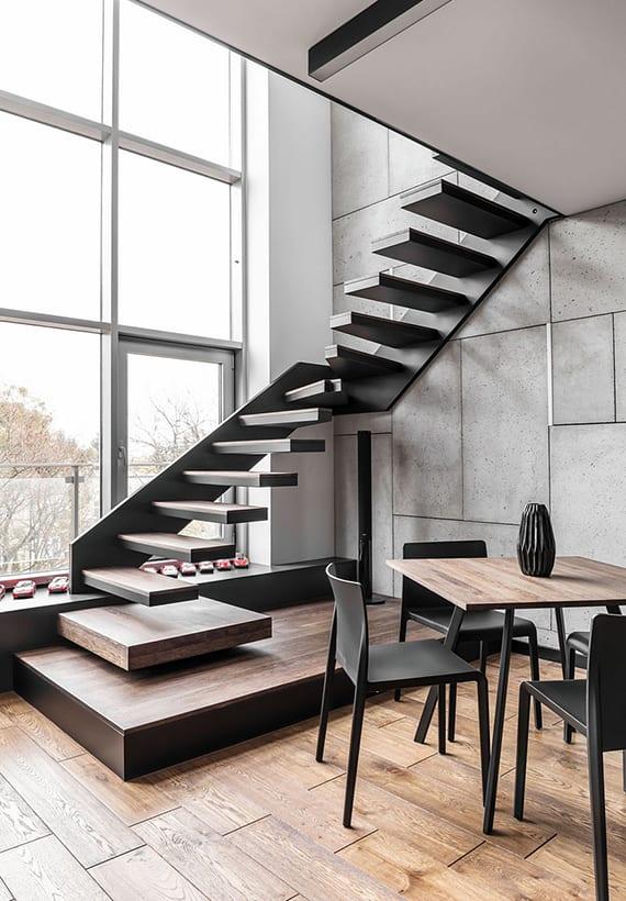 coole raumgestaltung wohnesszimmer mit pfosten-riegel-fassade, wandferkleidung mit betonplatten und einbauleuchten, kragtreppe mit holzstufen, rechteckigem esstisch holz mit schwarzen stühlen und holzbodenbelag
