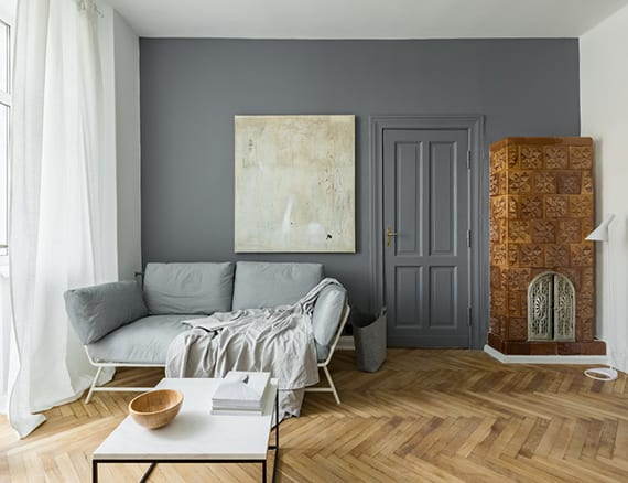 moderne wohnzimmergestaltung mit parkettboden, wandfarbe grau, eckkamin mit glasierten wandfliesen braun, modernem 2er sofa hellgrau, metallcouchtisch rechteckig und wanddeko mit großem bild