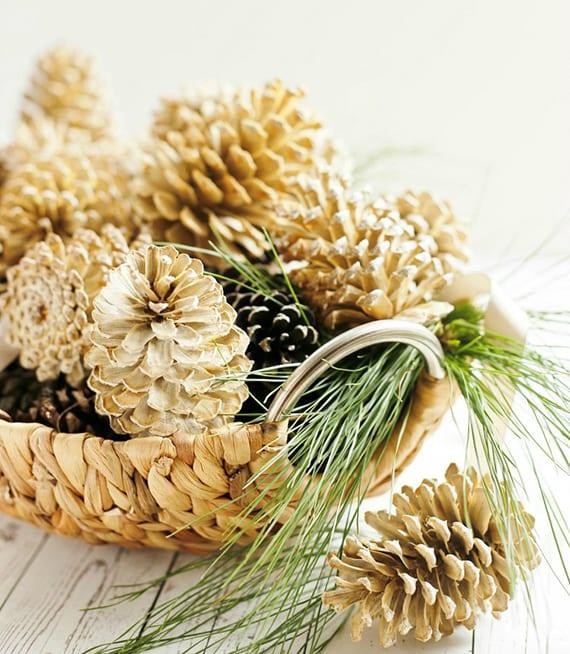 rustikale und moderne dekoidee für herbstliche oder winterliche tischdeko mit natürlichen und goldenen zapfen mit nadelbaumzweig in runder strohschale