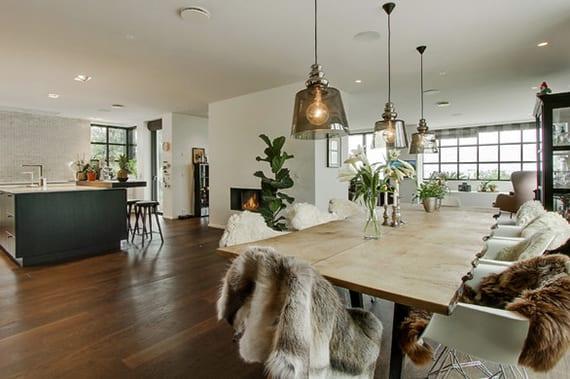 großzügiges wohnzimmer im skaninavischen wohstil gestalten mit masiivholztisch, weißen esszimmerstühlen mit pelzen, modernen pendellampen rauchglas