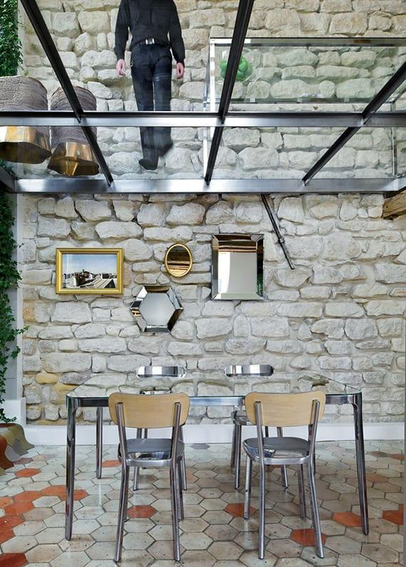 wohnideen für modernes interieur und kreative Esszimmergestaltung mit Glasboden, Kalksteinwand mit spigeln, esstisch mit alustühlen und hexagon bodenfliesen im grau und orange
