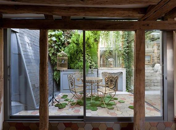 dachwohnung mit garten, französische fenster mit schiebetüren zum hofgarten mit hexagonfliesen, kamin und begrünter wand