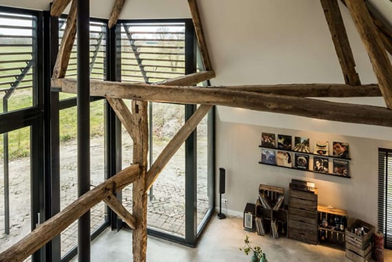 coole gestaltung wohnzimmer mit festferglasung in schwarzen rahmen, außen sonnenschutz mit lamellen, poliertem betonboden, wandfarbe grau, rustikale dekoration mit holozkisten und holzdachkonstruktion