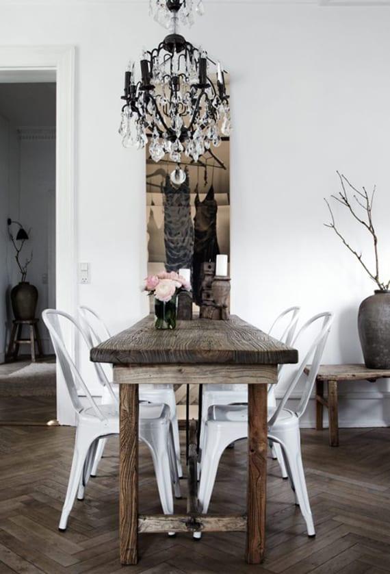 esszimmer im skandinavischen stil mit parkett, rustikalem esstisch massivholz,weißen metallstühlen und schwarzem Gothic-Kronleuchter mit kristallen