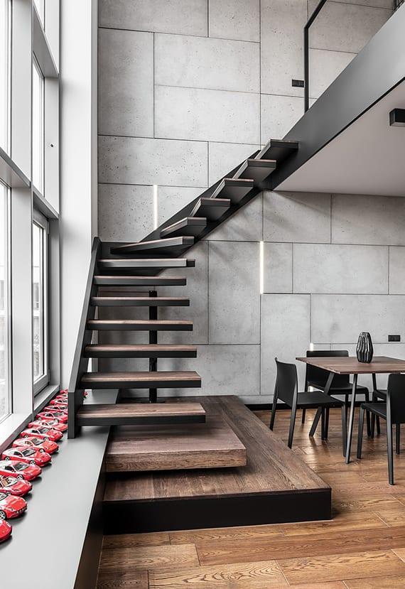 individuelle raumgestaltung mit kragtreppe, betonwandverkleidung mit LED-Wandleuchten, holzbodenbelag und raumhoher verglasung